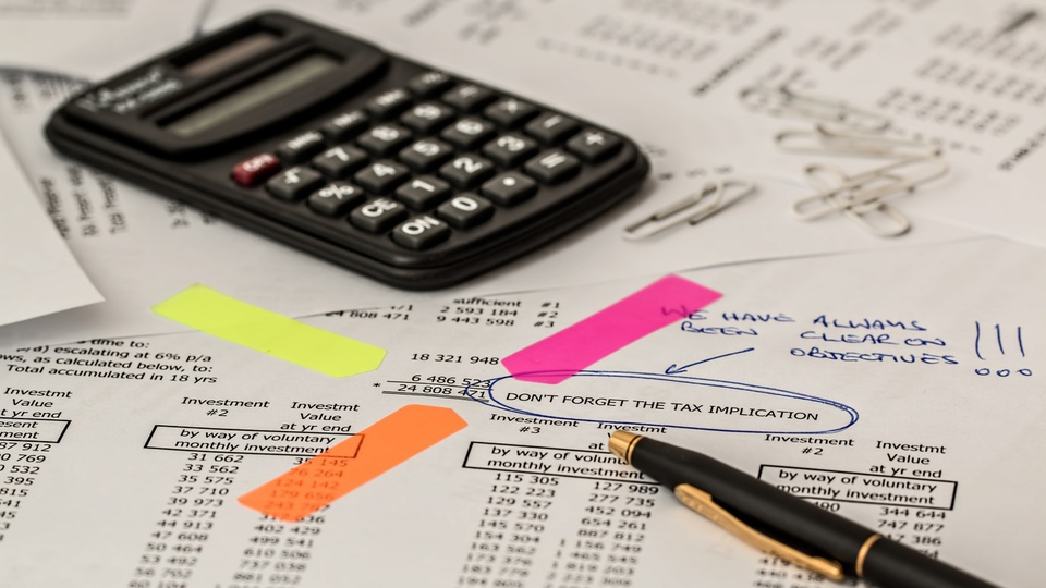 Câmara de Braço do Trombudo - SC: papéis com planilhas sob a mesa; calculadora e caneta sob os papéis