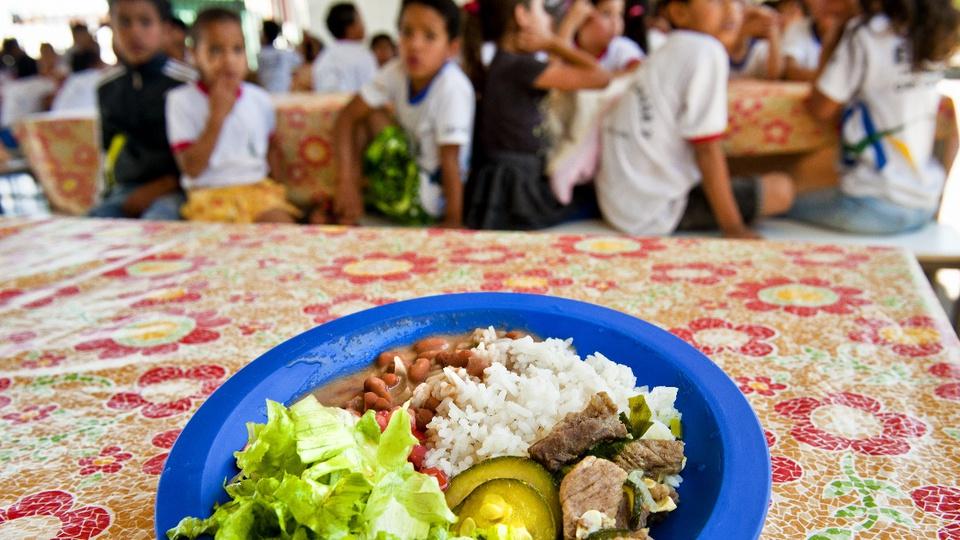Alunos da rede municipal de SP poderão solicitar vale-alimentação: é possível ver um prato de comida em cima de mesa. Ao fundo, desfocado, crianças olham na direção da câmera