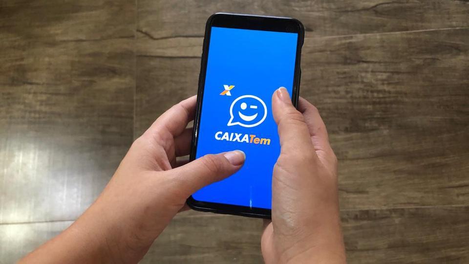 poupança digital: pessoa segurando celular aberto no aplicativo Caixa Tem