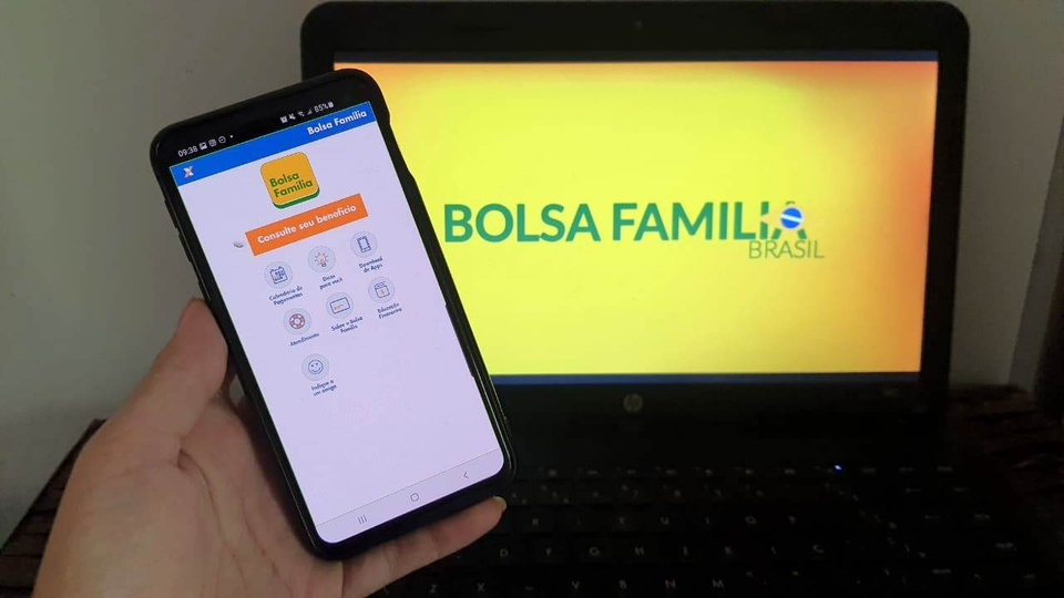aplicativo do Bolsa Família: mão segurando celular aberto no aplicativo do Bolsa Família