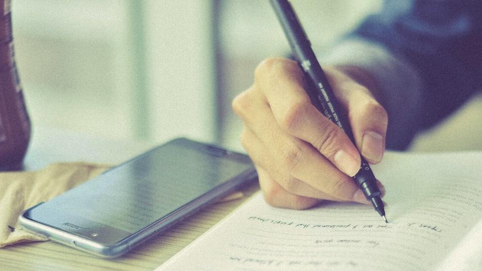 Aplicativos para estudar para concurso: pessoa escrevendo em caderno que está disposto sobre mesa. Só é possível ver a mão segurando a caneta enquanto a pessoa escreve. Ao lado, um celular está disposto na mesma mesa