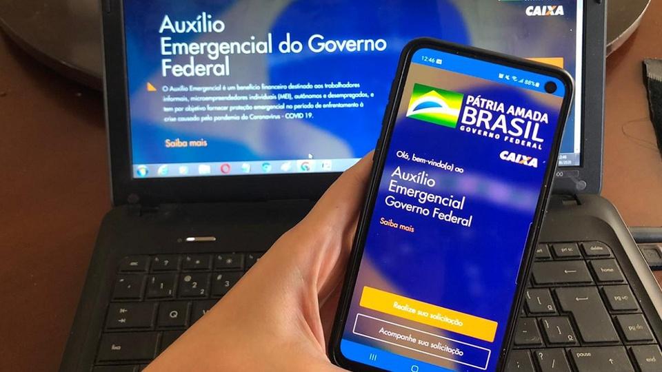 1,9 milhão de brasileiros seguem sem auxílio emergencial: enquadramento fechado em mão segurando em celular. Na tela do dispositivo, é possível ver a página inicial do aplicativo da Caixa Auxílio Emergencial. No fundo da foto, também consta um notebook