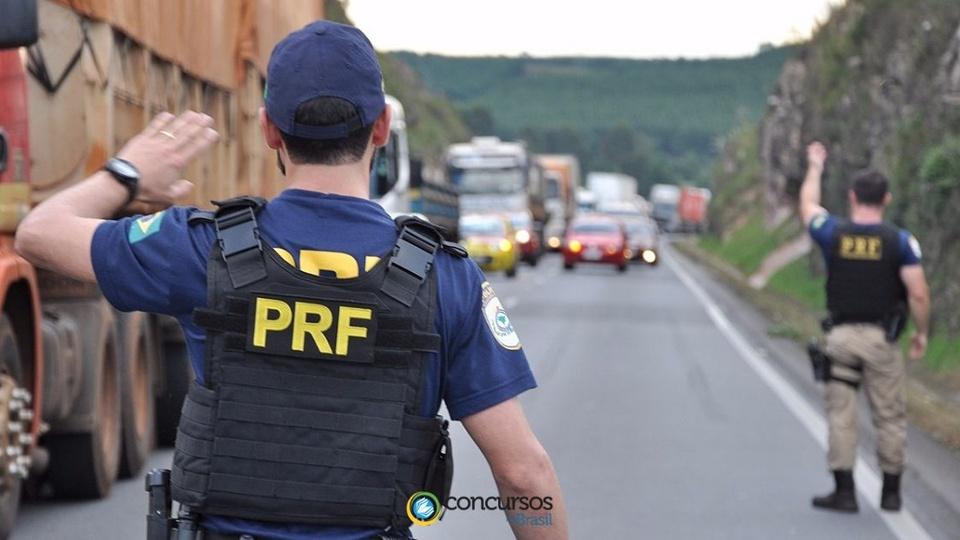 Aposentadoria integral aos policiais: polícia rodoviário federal, de costas, em rodovia. Ele está fazendo sinal para os carros passarem