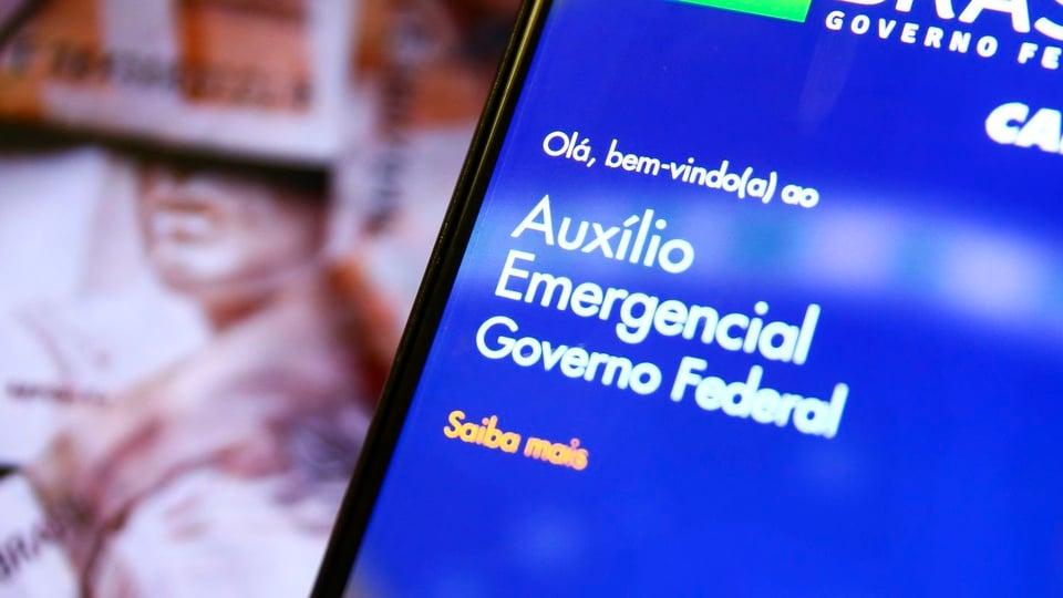Até quando pode devolver o auxílio emergencial indevido: tela de celular em que aparece página do auxílio emergencial