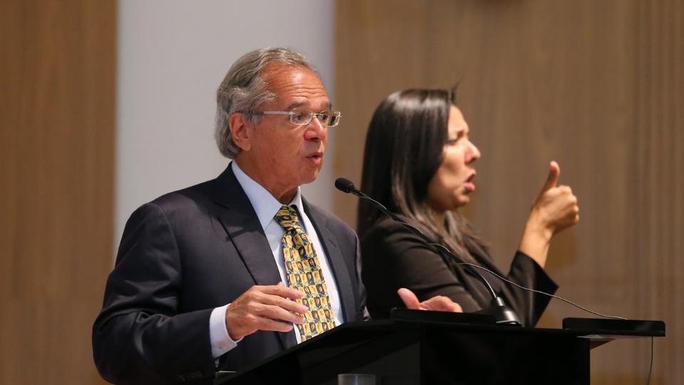 Autorizado novo processo seletivo Ministério da Economia: Paulo Guedes em pronunciamento. Ao seu lado, é possível ver uma intérprete de libras