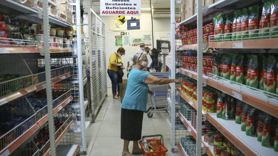Auxílio alimentar Curitiba: senhora, com máscara, pegando produtos em Armazém da Família, em Curitiba