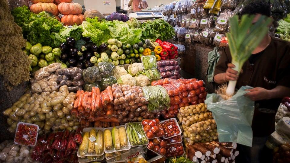 Auxílio cesta básica: a imagem mostra pessoa segurando um vegetal ao lado de banca de verduras no supermercado