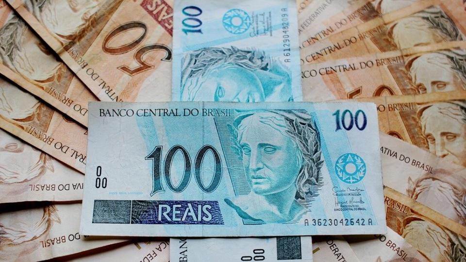 Auxílio de R$ 300 no Rio de Janeiro: notas de cem reais em destaque. Ao redor, é possível ver notas de cinquenta reais