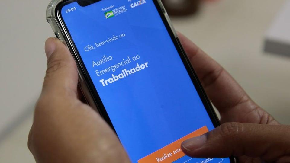 Contestações do auxílio emergencial em 2021: mão segurando celular. Na tela, é possível ver a página do auxílio emergencial