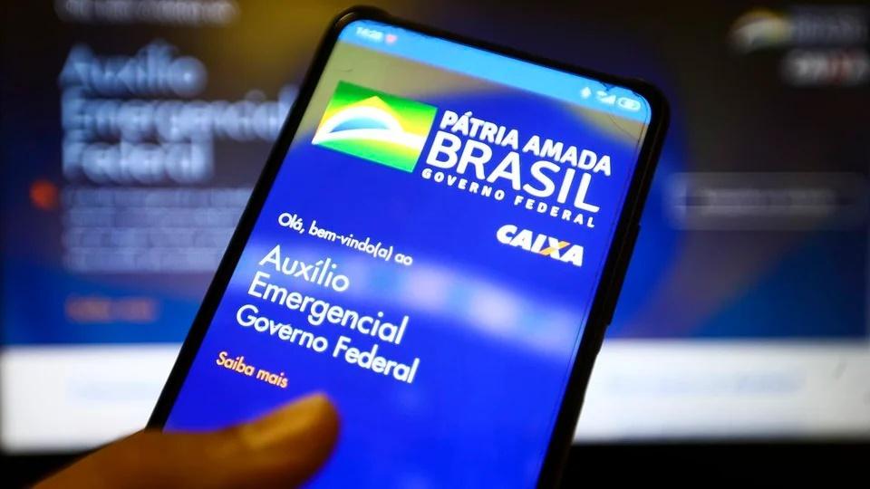 Quando começa o pagamento do auxílio emergencial 2021: enquadramento em mão segurando celular. Na tela do aparelho, é possível ver a página do auxílio emergencial