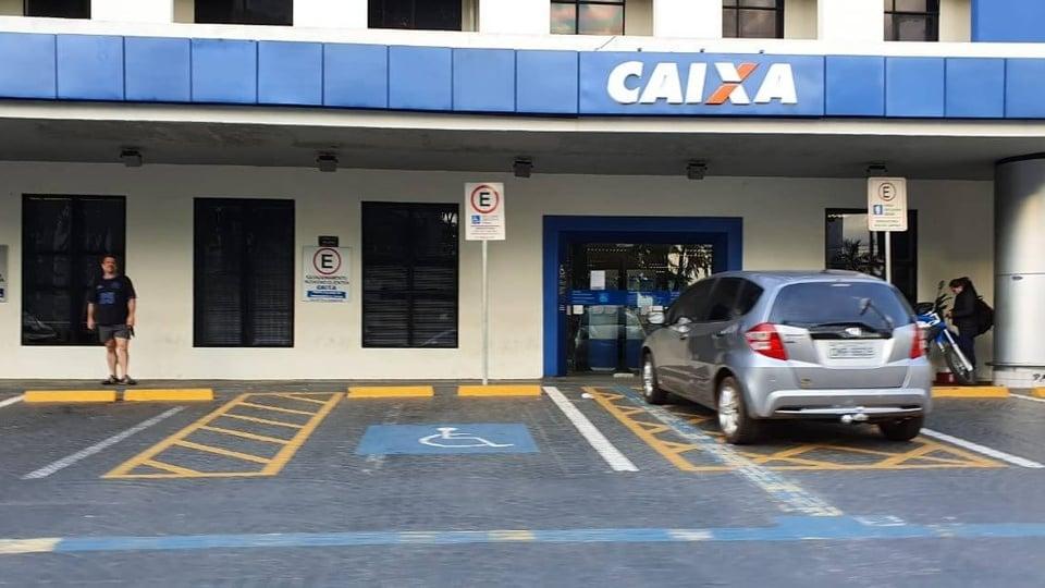 auxílio emergencial 2021: a imagem mostra fachada de agência da Caixa com carro estacionado na porta