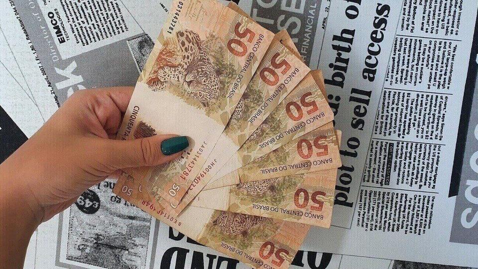 auxílio emergencial de R$ 1.000: a imagem mostra mão segurando um leque de notas de 50 reais