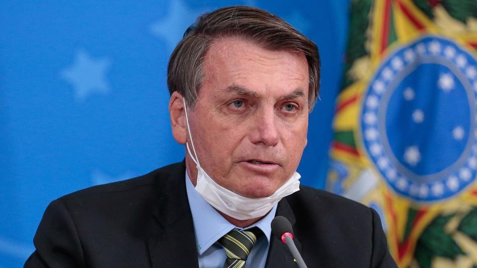 auxílio emergencial 2021: a imagem mostra jair bolsonaro com máscara cirúrgica no queixo falando em microfone