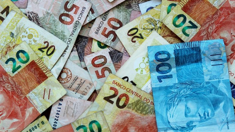 auxílio emergencial: a imagem mostra várias cédulas de dinheiro espalhadas