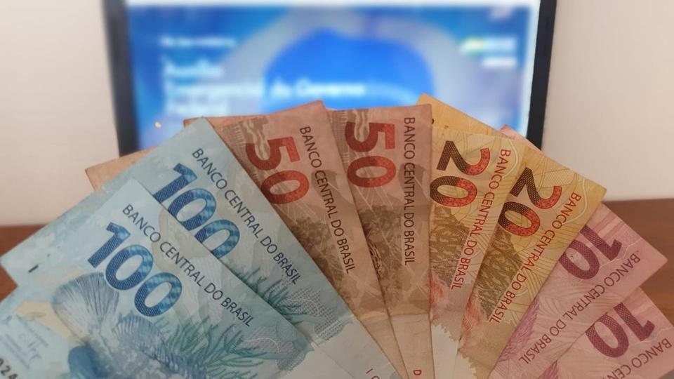 Auxílio emergencial foi a única renda para 4,4 milhões de brasileiros, cédulas de reais em frente a um notebook
