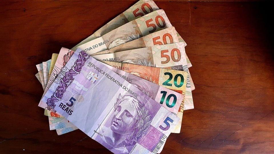 auxílio emergencial: leque de notas de 50, 20, 10 e 5 reais sobre mesa de madeira