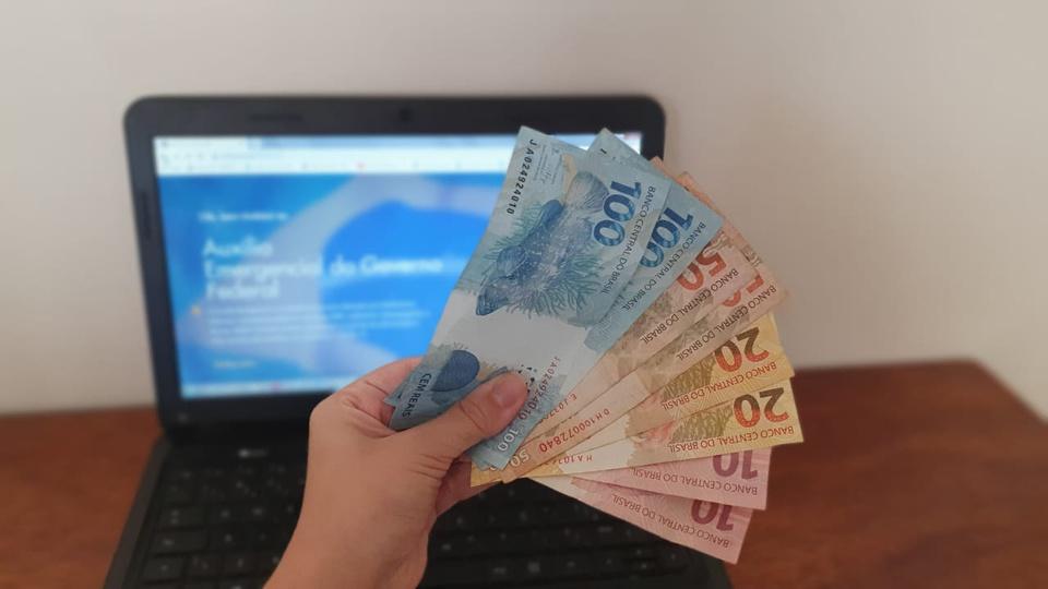auxilio emergencial: a imagem mostra mão segurando leque de dinheiro em frente a computador