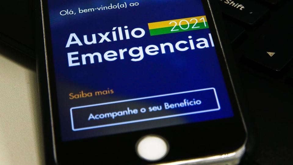 """Auxílio emergencial: orçamento do benefício tem """"sobras"""", smartphone aberto no aplicativo do auxílio emergencial"""