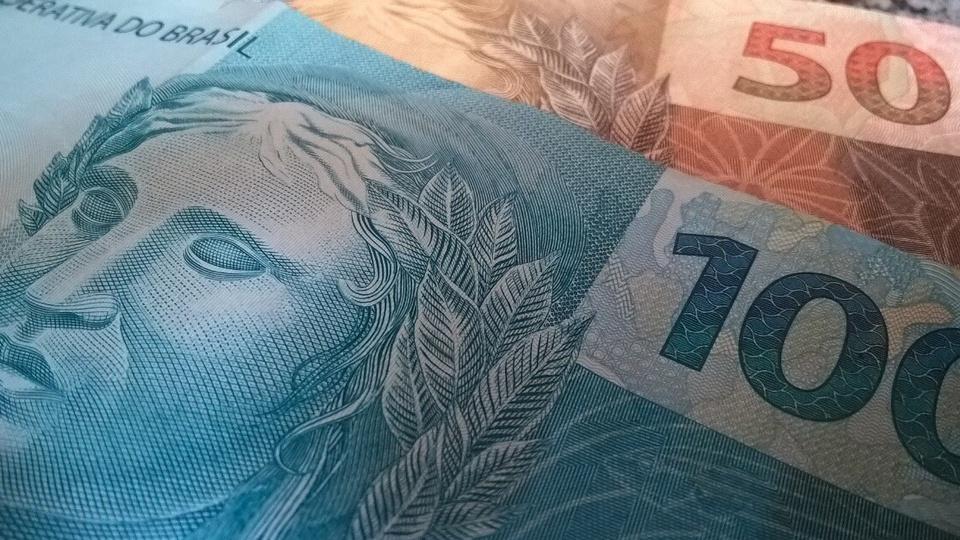 Auxílio emergencial pode gerar ganho médio de 2,46% no PIB: enquadramento fechado em duas cédulas de dinheiro, uma de cem e outra de cinquenta reais
