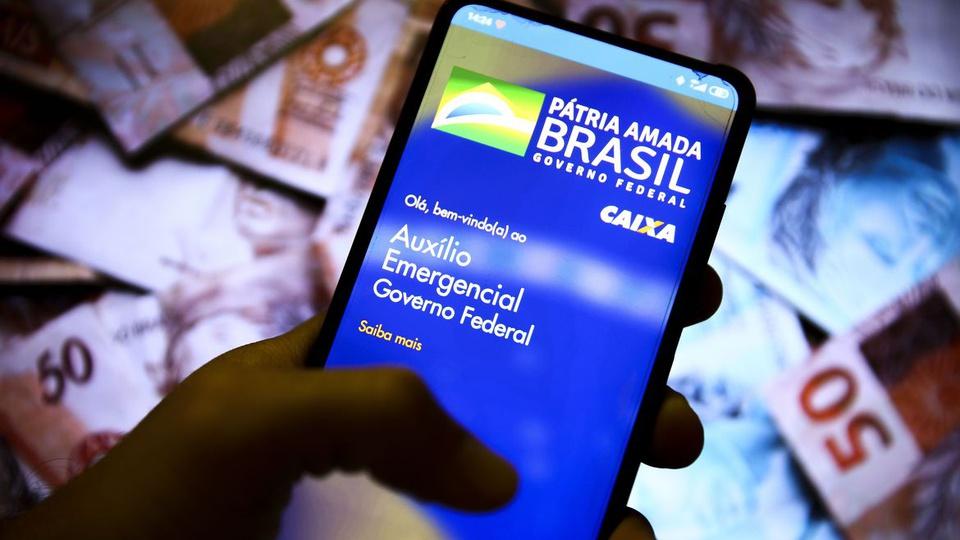 Auxílio emergencial 2021 prorrogado: mão segurando celular. Na tela, página do auxílio emergencial do governo brasileiro