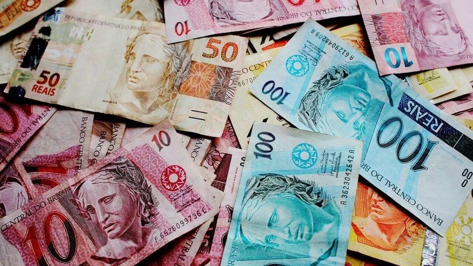 Devolver o auxílio emergencial: várias cédulas de dinheiro jogadas