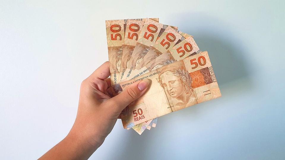 benefício emergencial: a imagem mostra mão segurando leque de dinheiro em notas de 50 reais