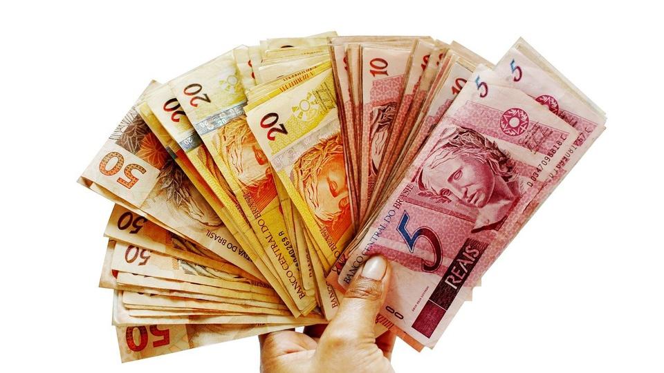 Benefícios sociais em 2021: uma mão segura notas de dinheiro