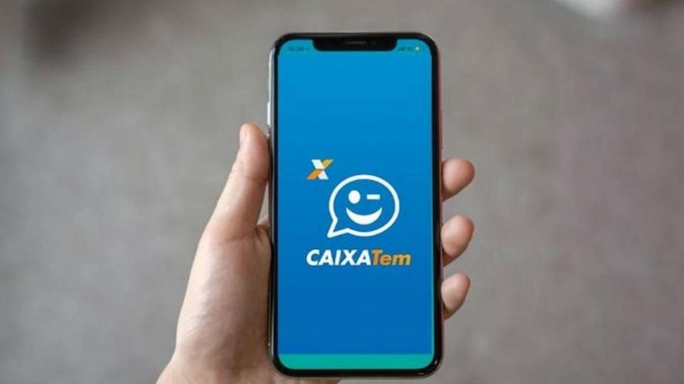 Como usar o cartão virtual Caixa Tem: mão segurando celular. Na tela do aparelho, é possível ver a página inicial do aplicativo Caixa Tem