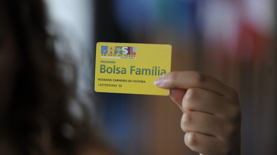 Valor do auxílio emergencial no bolsa família de março: mão segurando cartão do Bolsa Família