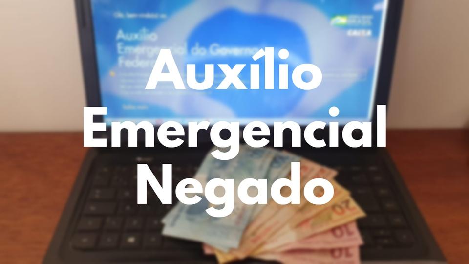 """contestar auxílio emergencial negado: a imagem borrada mostra computador aberto no site do auxílio emergencial com notas de dinheiro em cima do teclado. Em cima da imagem está escrito """"Auxílio emergencial negado"""""""