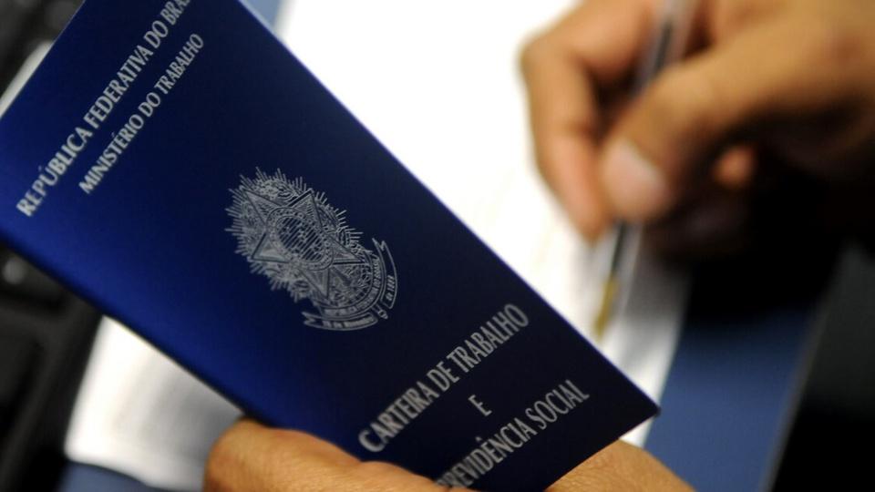 Bolsonaro amplia prazo para suspensão de contratos: enquadramento fechado em mão segurando uma carteira de trabalho aberta. No fundo, é possível ver a mesma pessoa escrevendo com a outra mão em papel