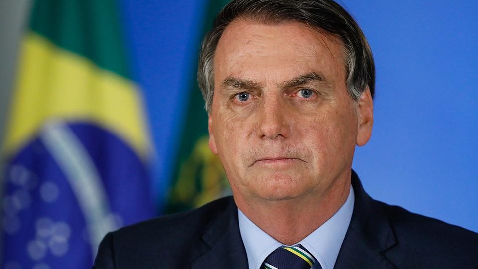 pec emergencial: a imagem mostra Jair Bolsonaro de terno e gravata com bandeira do brasil ao fundo