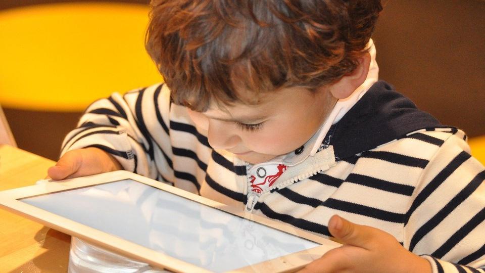 Acesso gratuito à internet para alunos: criança mexendo em tablet
