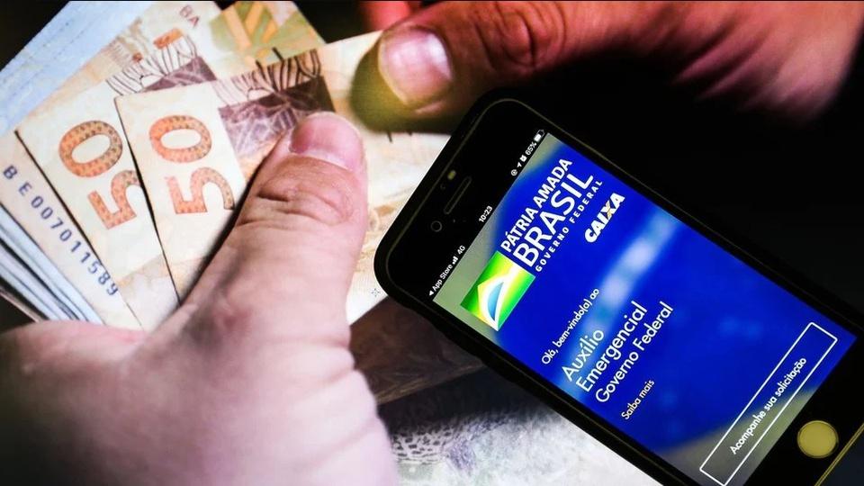 Caixa registra filas para saques do auxílio emergencial, mão segurando dinheiro e celular
