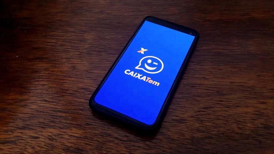 Como fazer pagamentos em lotéricas sem cartão: celular disposto em superfície plana. Na tela, é possível ver a página inicial do aplicativo Caixa Tem