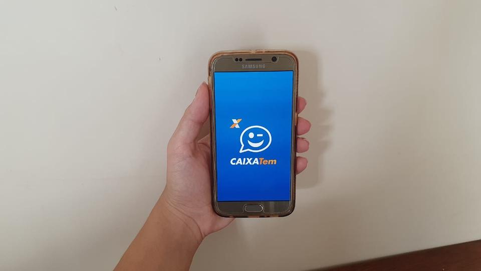 Caixa Tem: mão segurando celular aberto no aplicativo Caixa Tem