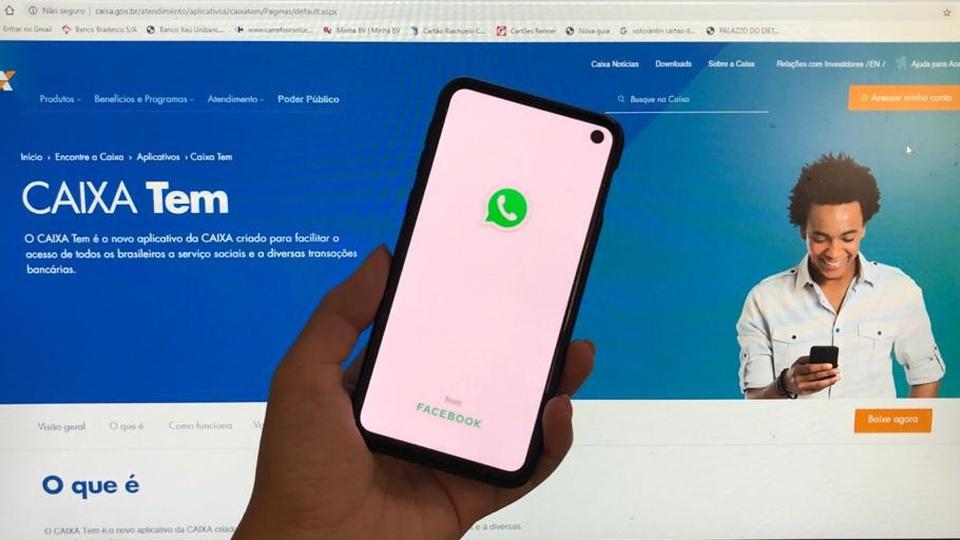 Caixa Tem: mão segurando celular aberto no whatsapp em frente a computador aberto no site do Caixa Tem