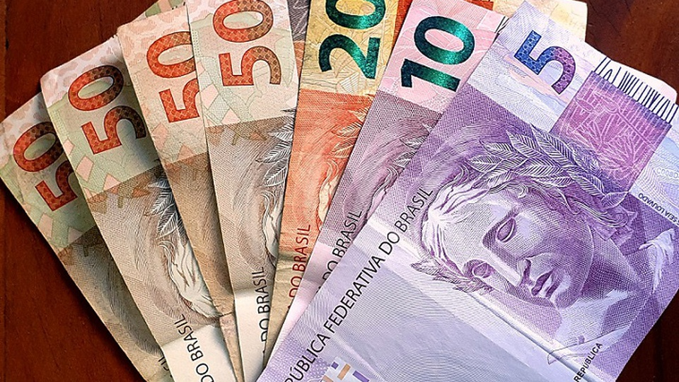 PIS PASEP: a imagem mostra um leque de notas de 5, 10, 20 e 50 reais sobre mesa de madeira