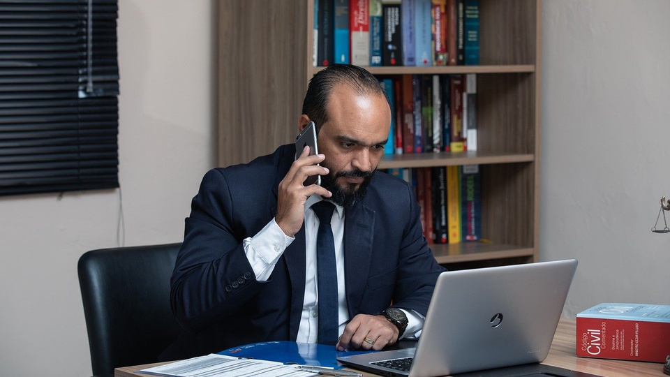 Processo seletivo Câmara de Natividade da Serra - SP: homem de terno em escritório, falando no celular