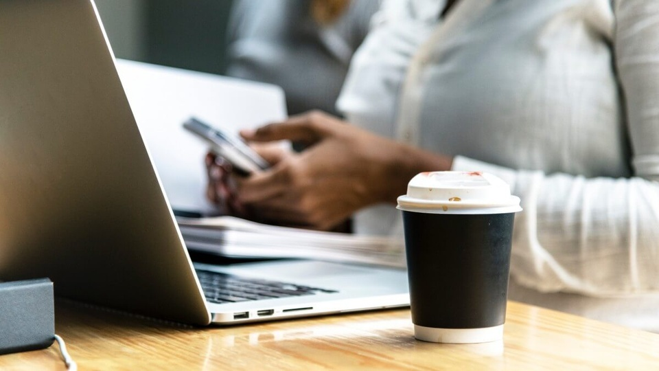 Emprego público:  a foto mostra pessoa segurando um celular diante de uma mesa contendo um notebook e um copo descartável no primeiro plano