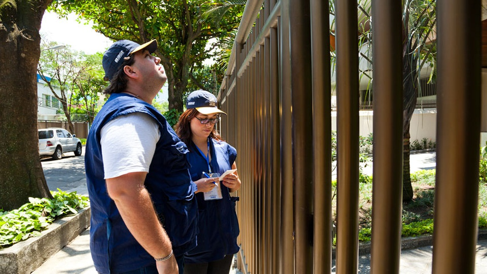 censo 2021: a imagem mostra dois servidores do IBGE em frente a portão de casa