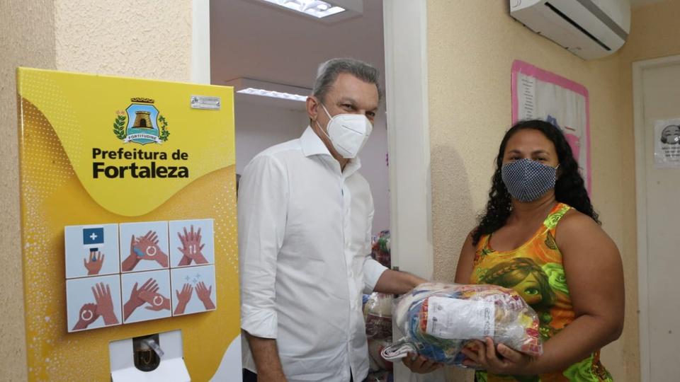 Cestas básicas para Bolsa Família em Fortaleza: mulher recebendo cesta básica em Fortaleza