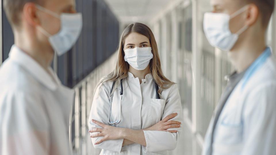 Prefeitura de Porto Seguro: três profissionais da saúde em pé; foco em um deles que é mulher e está de máscara e com estetoscópio no pescoço