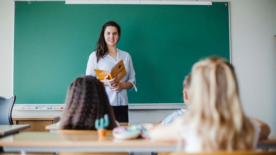 Prefeitura de Vargeão: a imagem mostra professora à frente da classe e duas alunas sentadas em suas carteiras