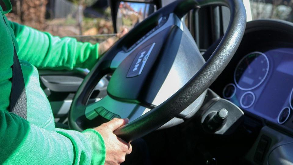 Processo seletivo CIDERSOP: pessoa dirigindo um caminhão. É possível ver apenas as mãos no volante