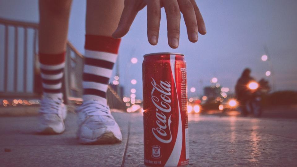 Coca-Cola abre 1.800 vagas de emprego pelo Brasil: lata de conca-cola no chão e mulher tenta pegá-la