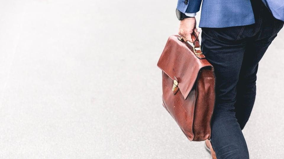 Servidor pode ser contratado sem certeza de estabilidade: homem segurando pasta de couro enquanto caminha. Só é possível vê-lo da cintura para baixo, de costas