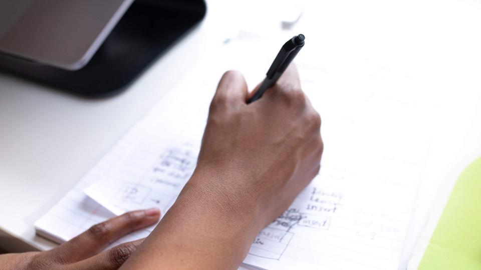 Começar a estudar para concurso: imagem mostra mão segurando caneta anotando algo em papel
