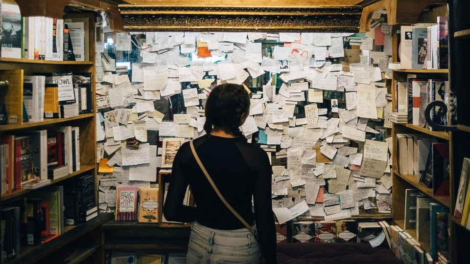 Como escolher um concurso: mulher de costas olhando para uma parede cheia de papéis. Em cima e ao redor, também é possível ver prateleiras