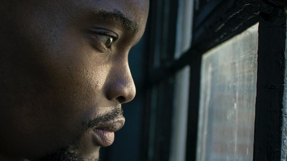 Como lidar com a ansiedade no estudo para concursos públicos: enquadramento fechado no rosto de um homem olhando para uma janela de maneira reflexiva